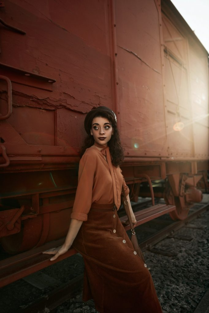 Woman wearing an outfit in analogous colors posing in front of train wagon