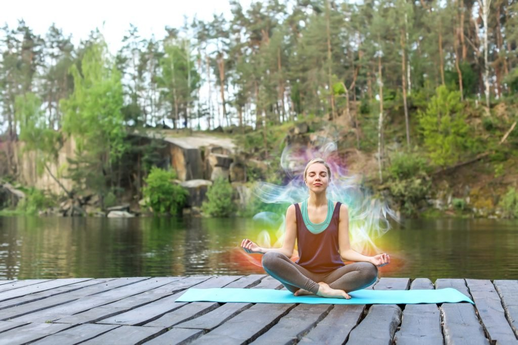 Woman sitting outdoors near river with aura colors around her body
