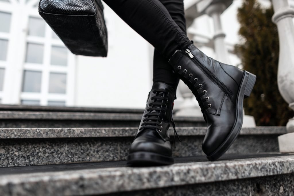 Woman in black leather shoes with a handbag standing on stone steps