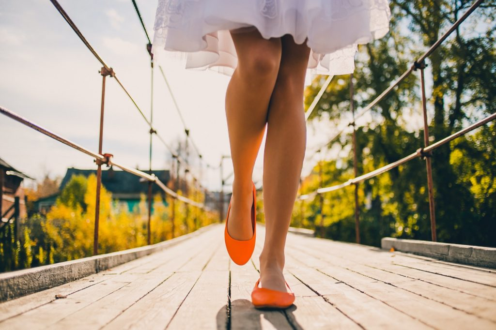 Woman with bright orange shoes walking on bridge in a park