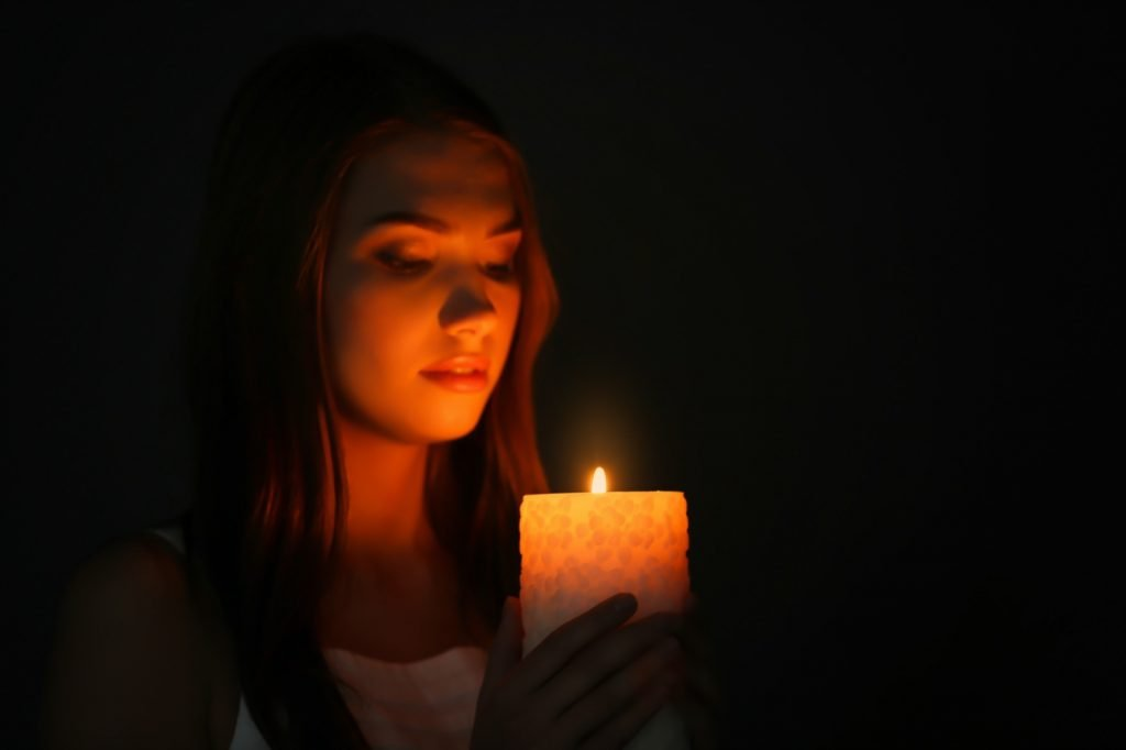Woman with specific intentions burning candle in darkness