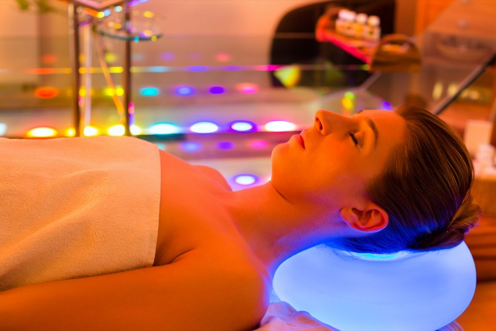 Woman enjoying color therapy in spa