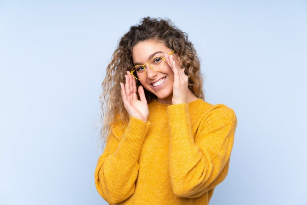 Blonde woman with curly hair and yellow glasses on blue background