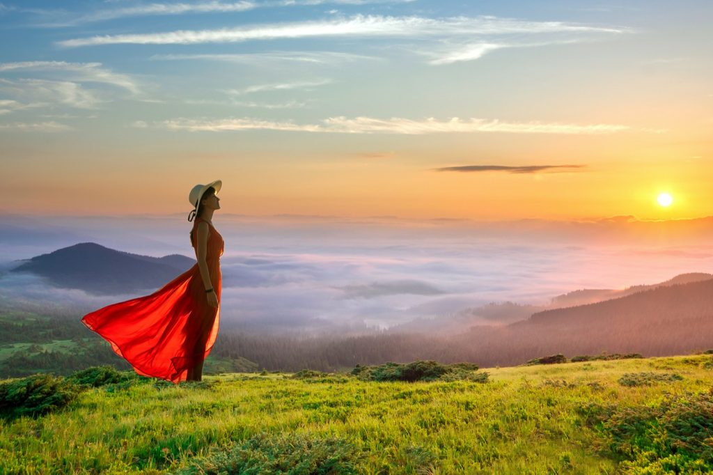 Woman in red colored long dress standing on mountains enjoying view of rising sun and white fog below