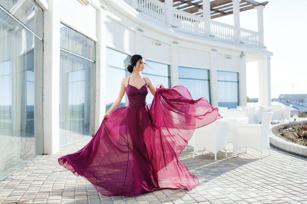 Woman in an elegant red-violet evening dress posing outdoors