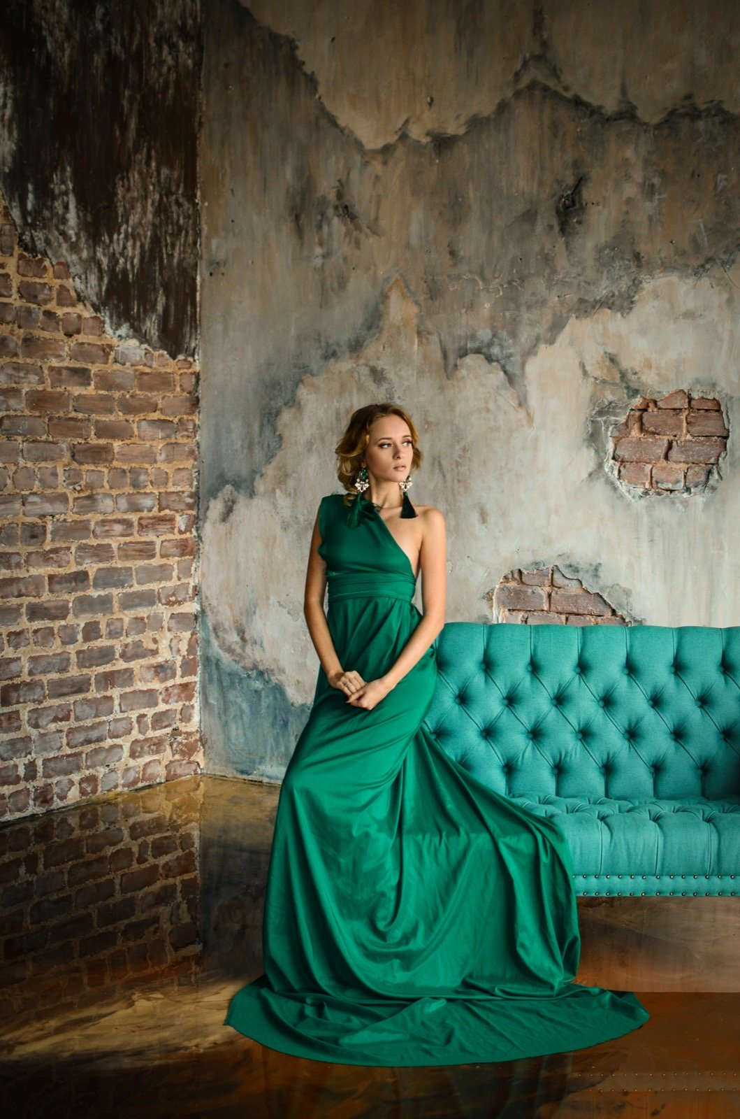 Fashion shot of woman in green dress posing in vintage interior setting