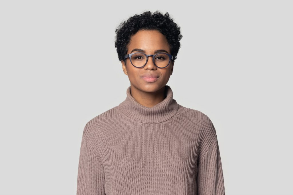 Woman wearing grey glasses and sweater posing in studio