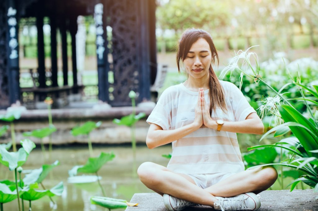 Woman with hand palms together practicing yin yang force calm and balanced in Chinese garden