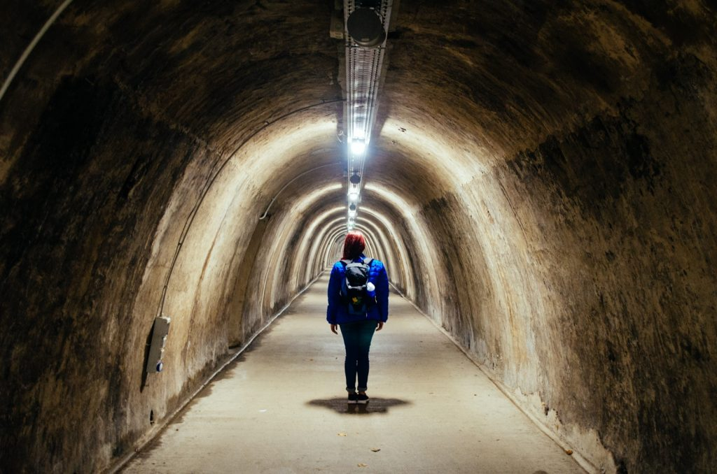 Woman with colorful clothes standing inside tunnel illuminated by fluorescent lamps