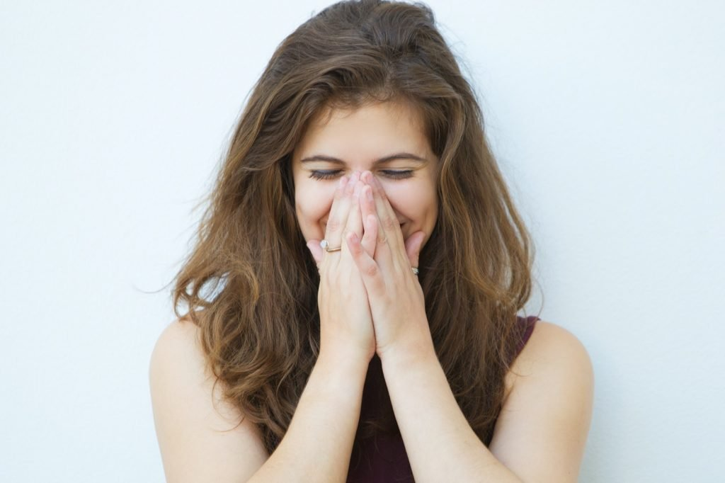 Woman laughing and covering her mouth with her hands