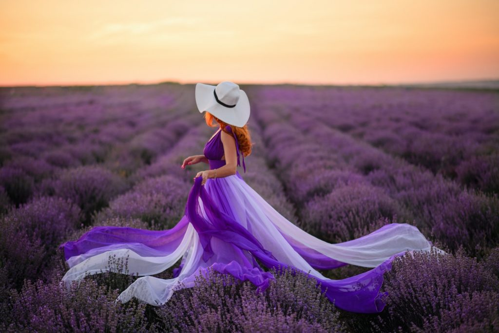 Redhead woman in luxurious modern purple dress standing in colorful lavender field