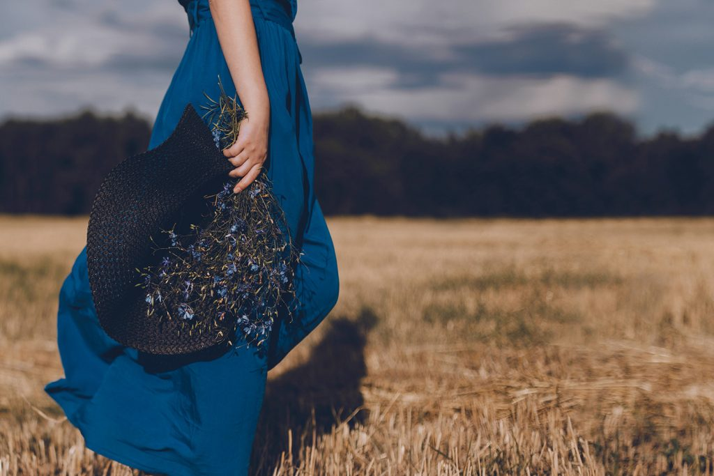 Woman in marine navy blue dress walking in field holding hat and bouquet