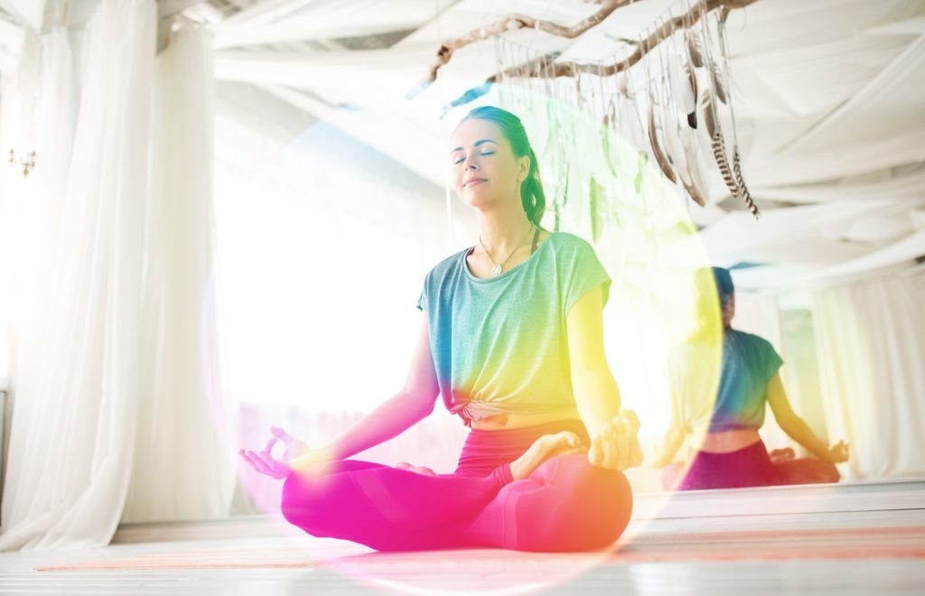 Woman meditating in a lotus pose with a rainbow aura around her