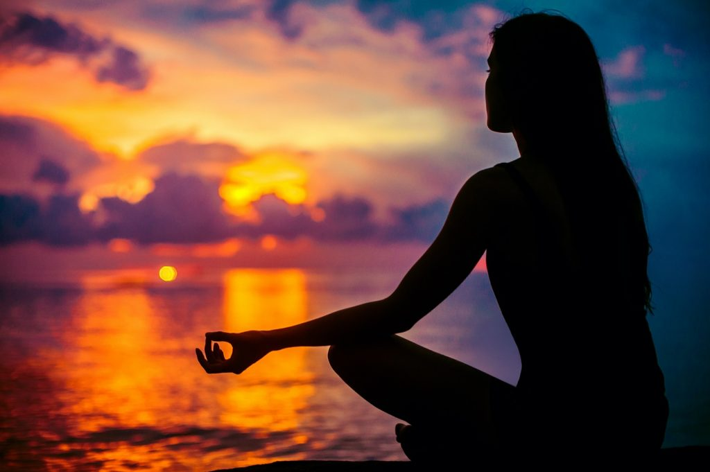 Spiritual woman meditating and relaxing in yoga pose at sunset