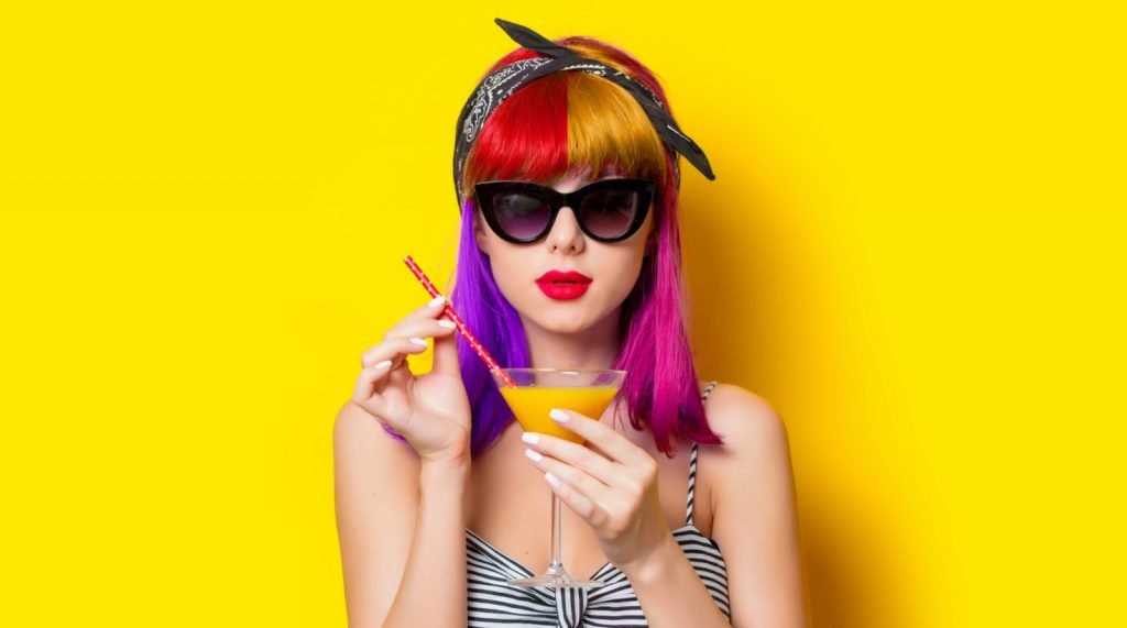 Woman with multicolored hair holding lemonade on yellow background