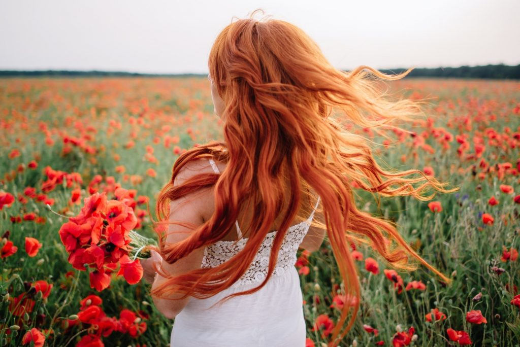 Woman with natural red hair standing in a poppy field