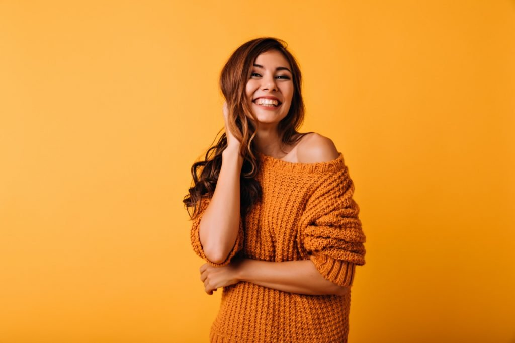 Woman in orange attire touching her brown wavy hair and laughing