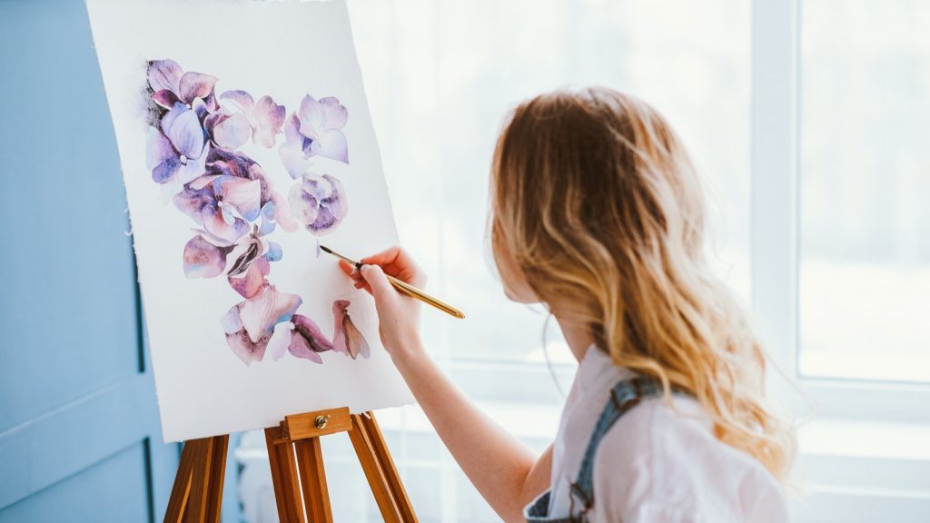 Woman painting beautiful watercolor floral design on a canvas