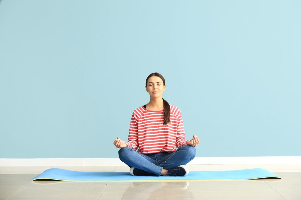 Woman practicing yoga on a mat in front of a blue colored wall