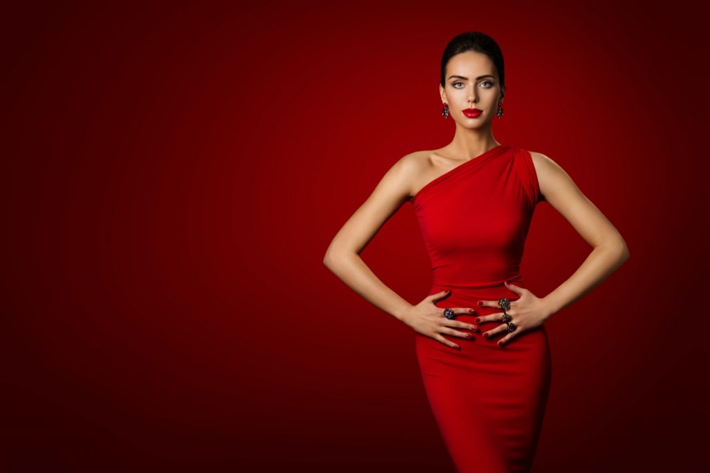 Portrait of woman in red dress photographed on red background