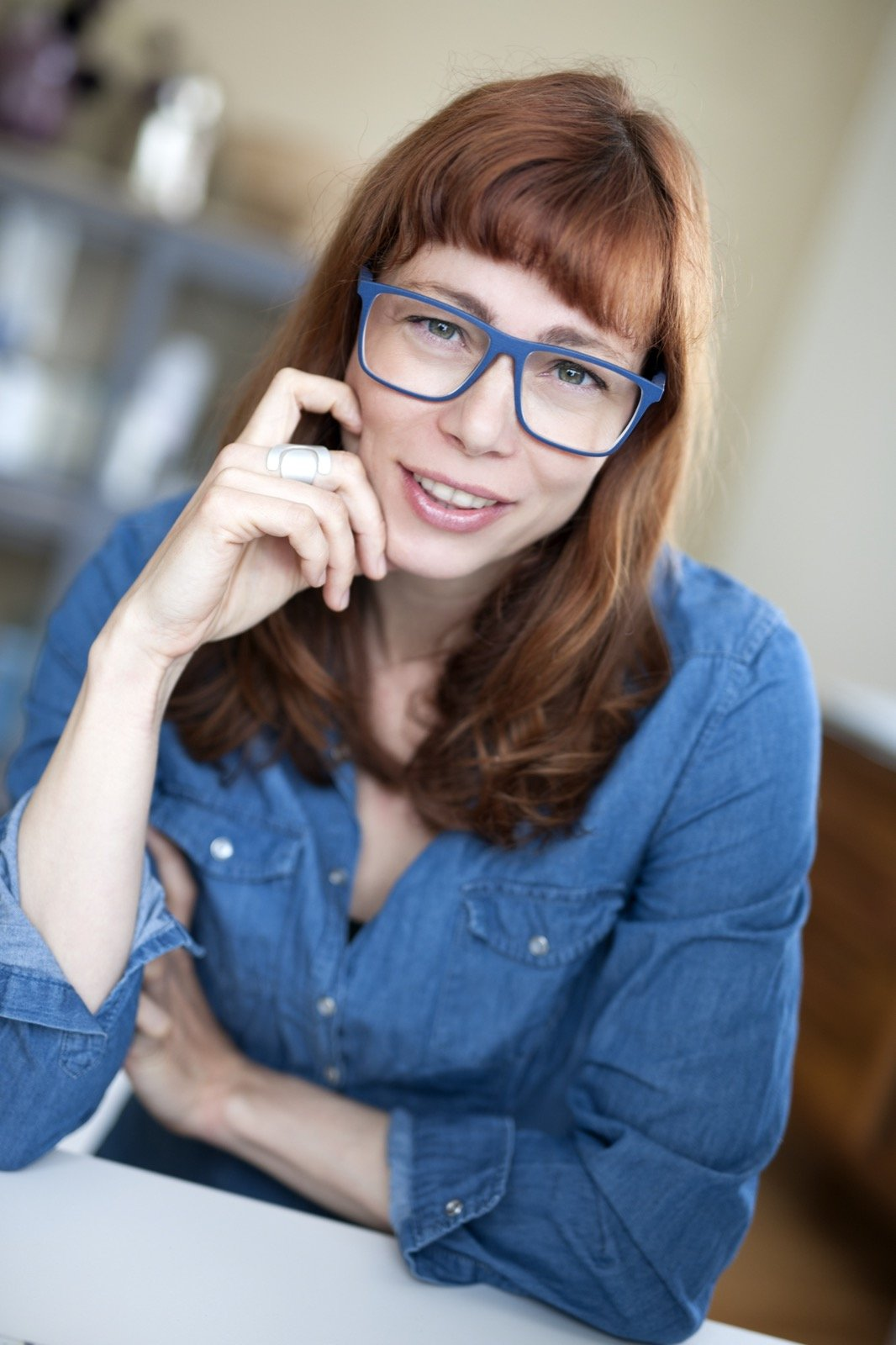 Woman with red hair and blue glasses