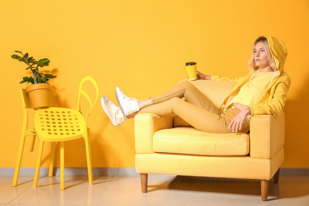 Fashionable woman relaxing in armchair. Everything is yellow