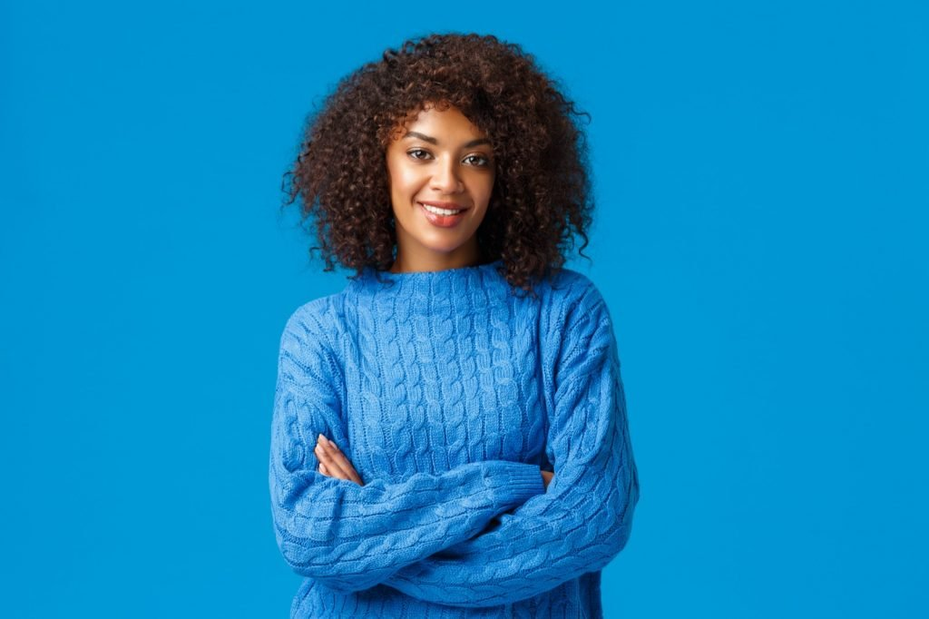 Confident African American woman with afro haircut in blue clothes