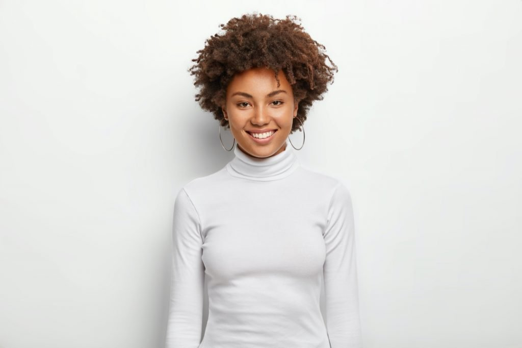 Woman with curly hair wears white casual clothes and poses in studio