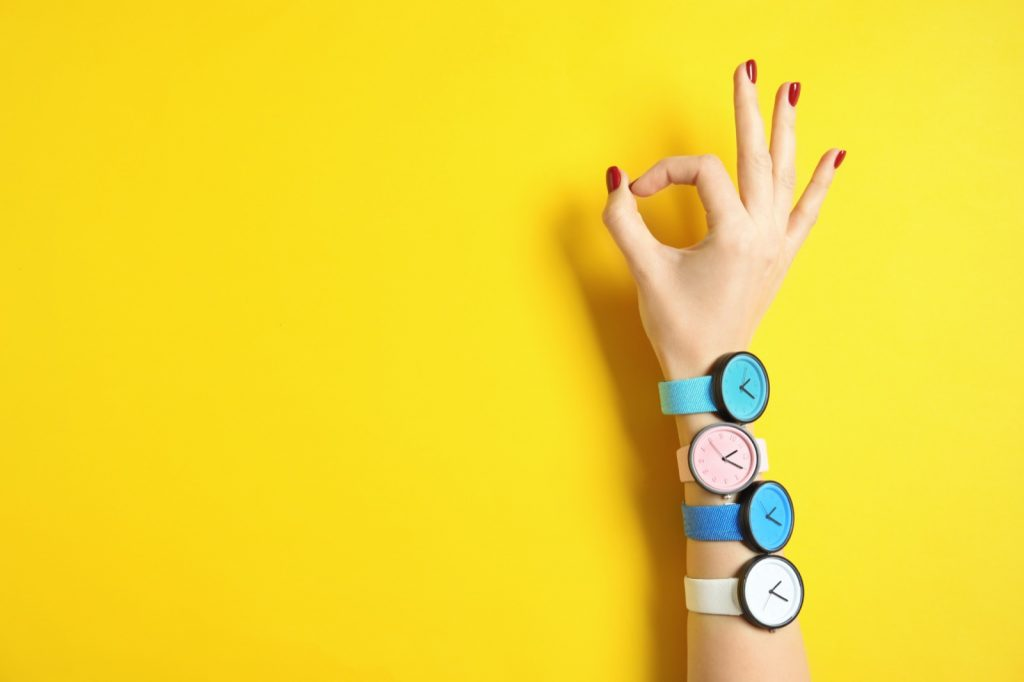 Woman wearing wrist watches in bright colors on yellow background