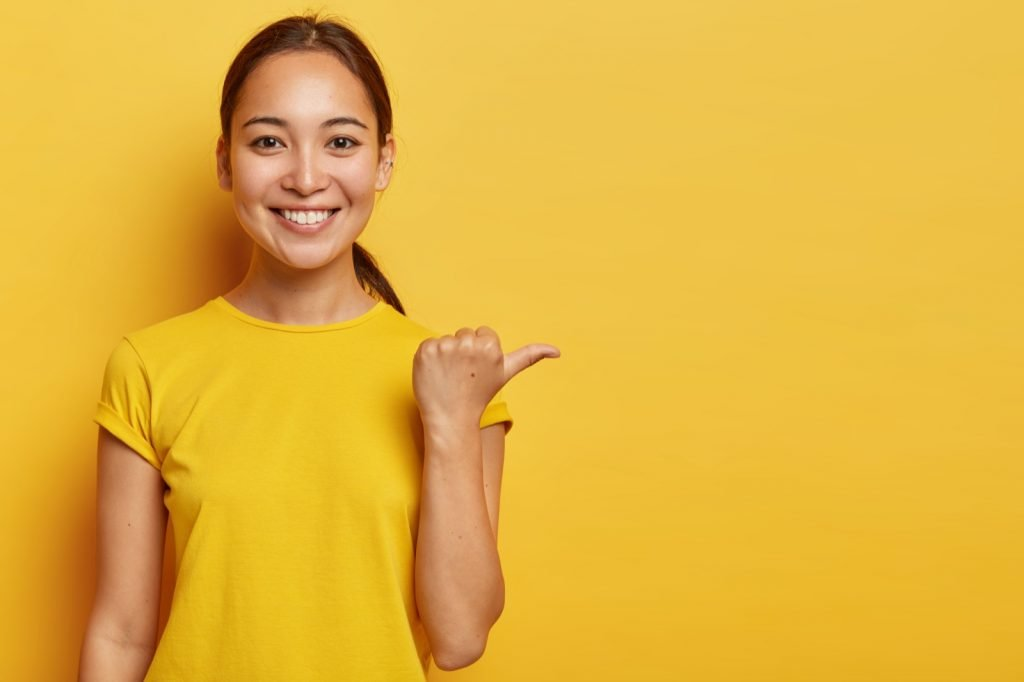 Portrait of cheerful Asian female wearing bright yellow clothes