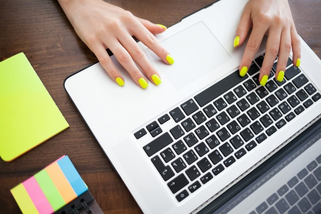 Woman's hands with neon yellow nails typing on a laptop