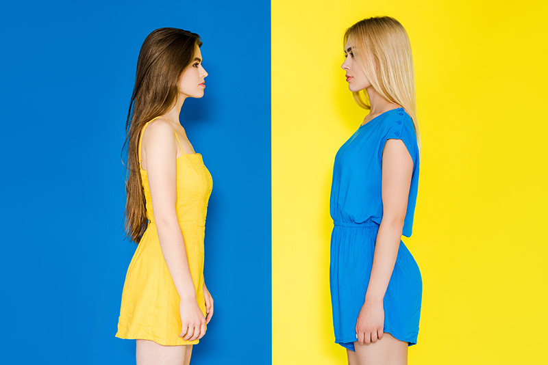 Two women looking at each other isolated on contrasting blue and yellow background
