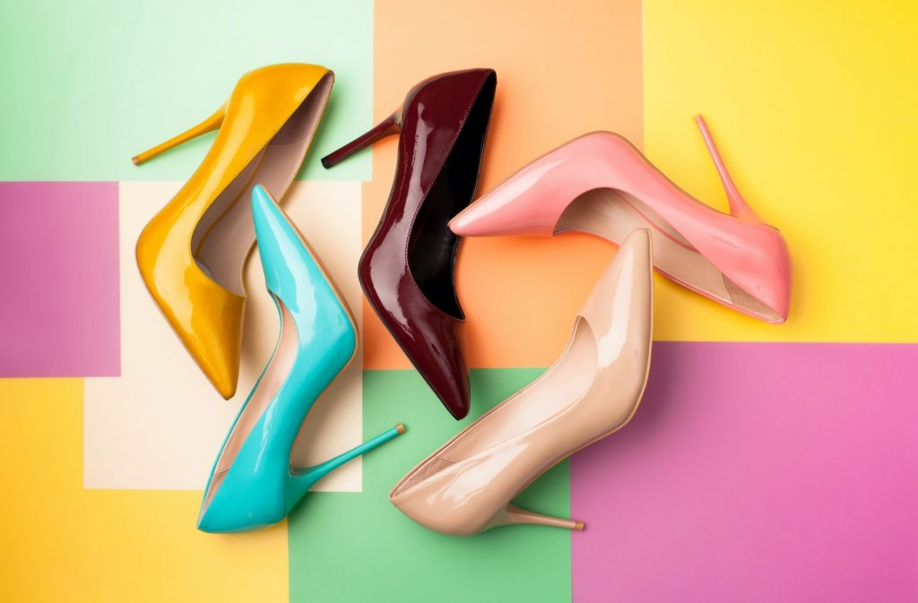 Set of bright colored women's shoes on a background with different colors