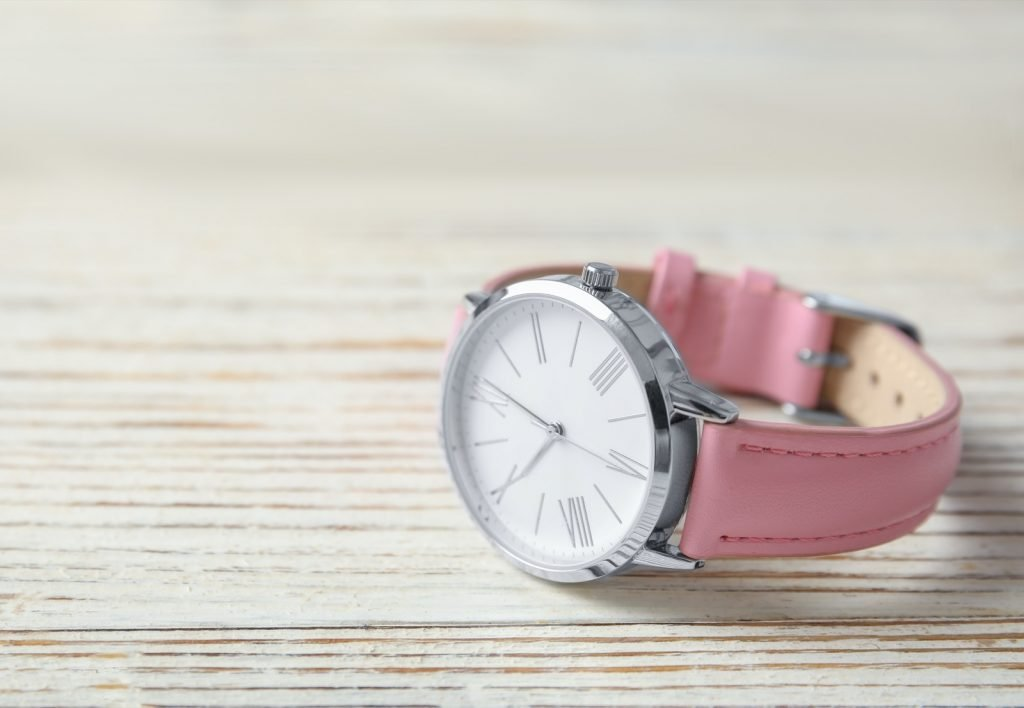 Women's wrist watch with pink leather strap on a wooden table