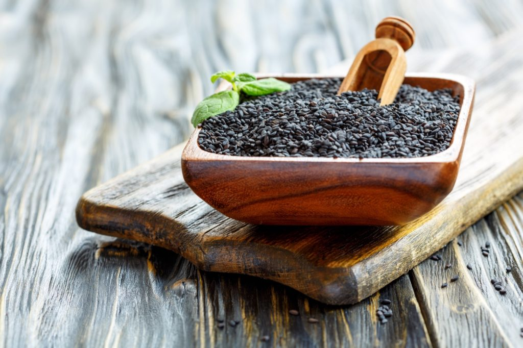 Wooden bowl of black sesame seeds and scoop