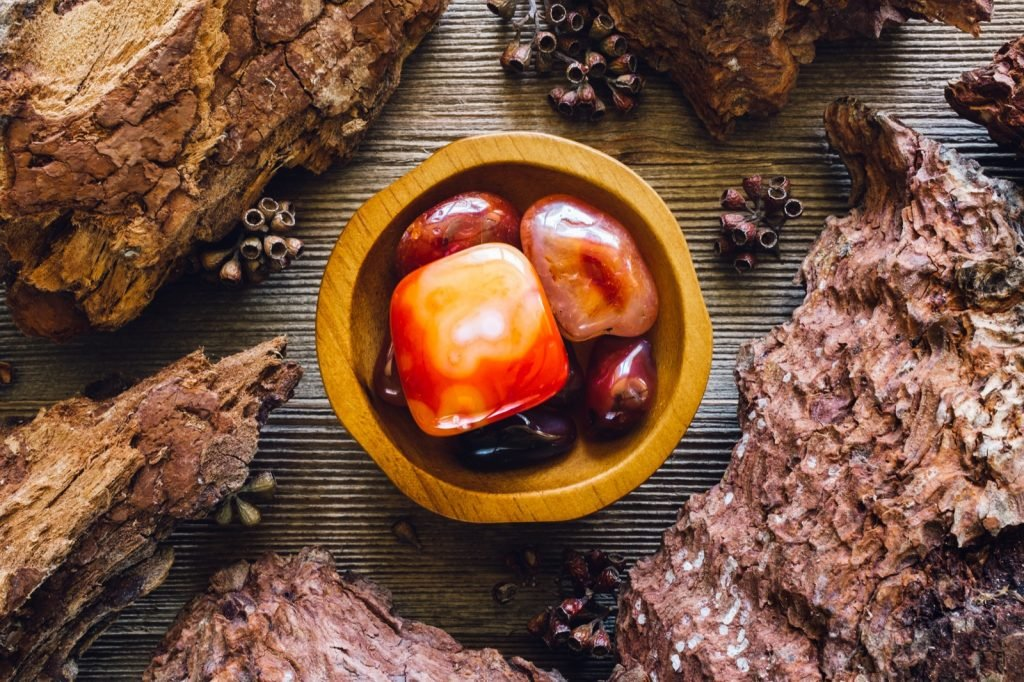 Wooden bowl with red colored carnelian stones