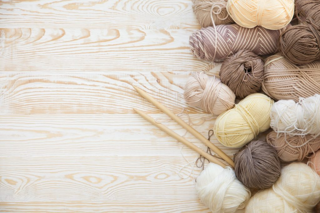Yarn in beige, brown, gray and white neutral colors lying on wooden table next to knitting needles