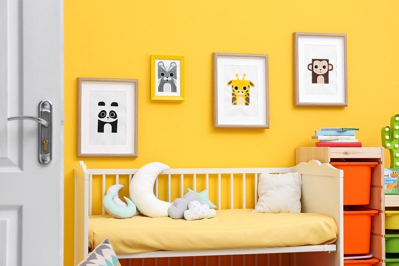 yellow Baby bedroom with pictures of animals on wall
