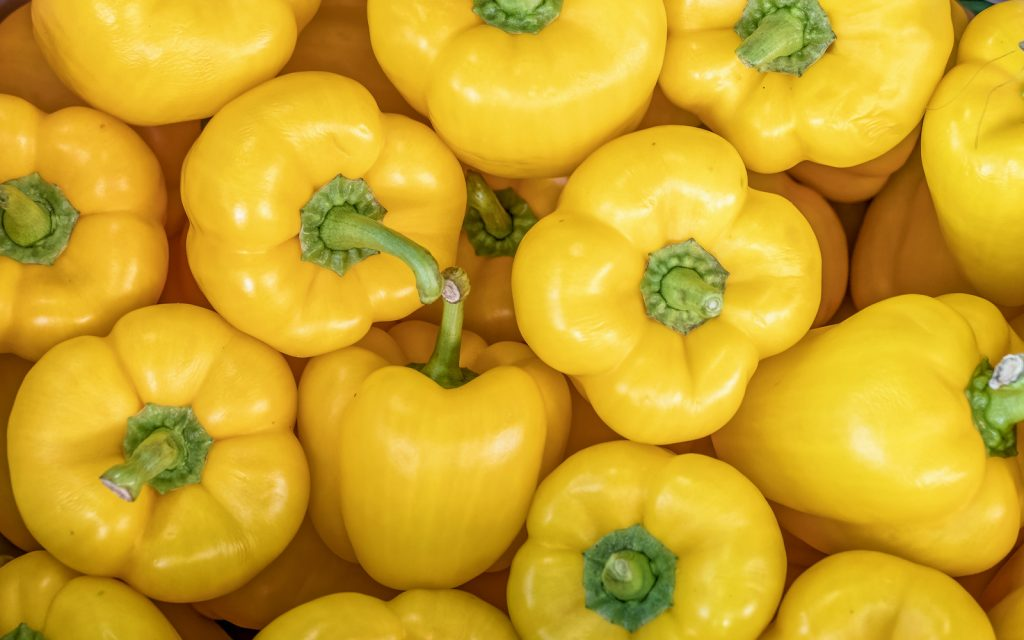 Closeup of a bunch of bright yellow bell peppers