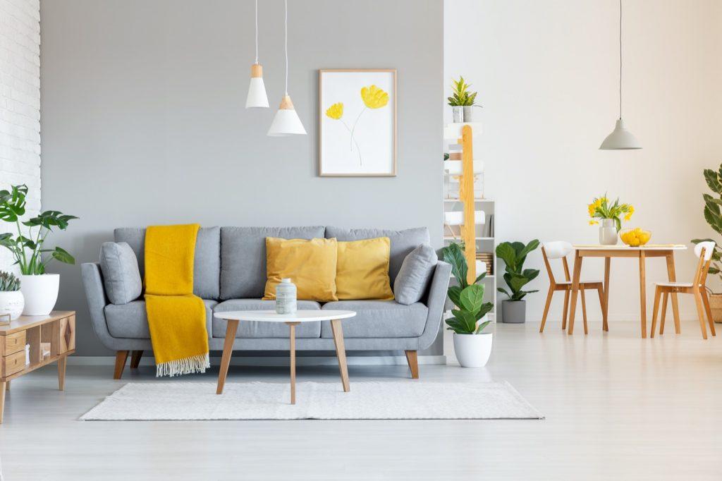 Yellow blanket on gray sofa in modern living room interior