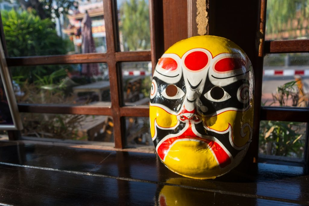 Yellow Chinese opera mask placed in front of a window