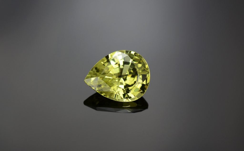 Natural bright lemon yellow color chrysoberyl, drop shaped faceted on grey background