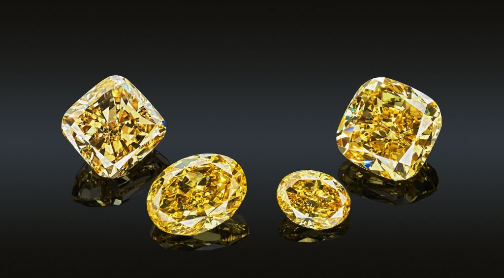 Closeup of 4 yellow diamonds in two different shapes, sizes and cuts reflected on black glass they are placed on