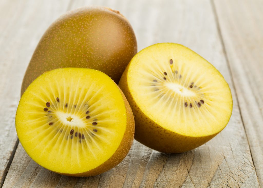 Whole and cut golden yellow kiwifruit on wooden cutting board