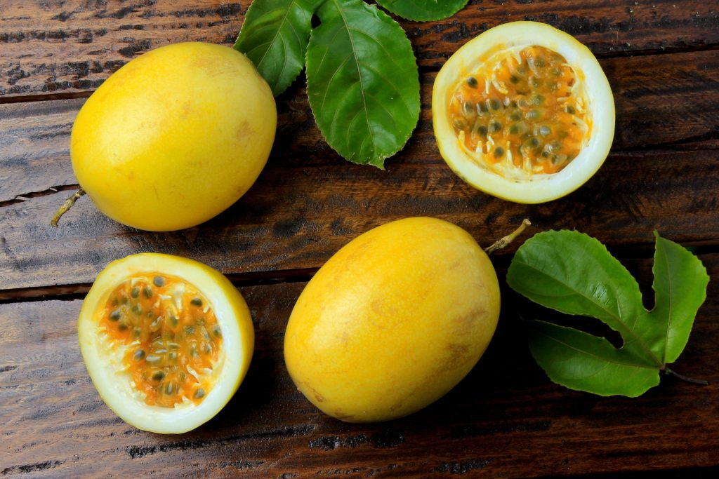 Yellow passion fruit with leaves and one passion fruit cut in half on rustic wooden table