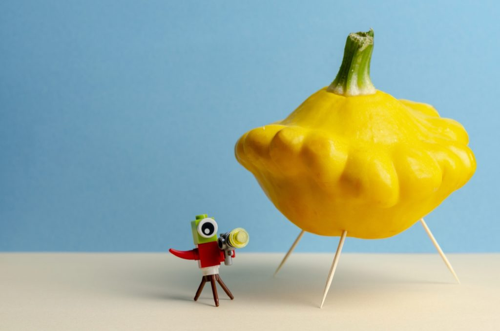 Yellow pattypan squash that looks like a ufo on a colored background
