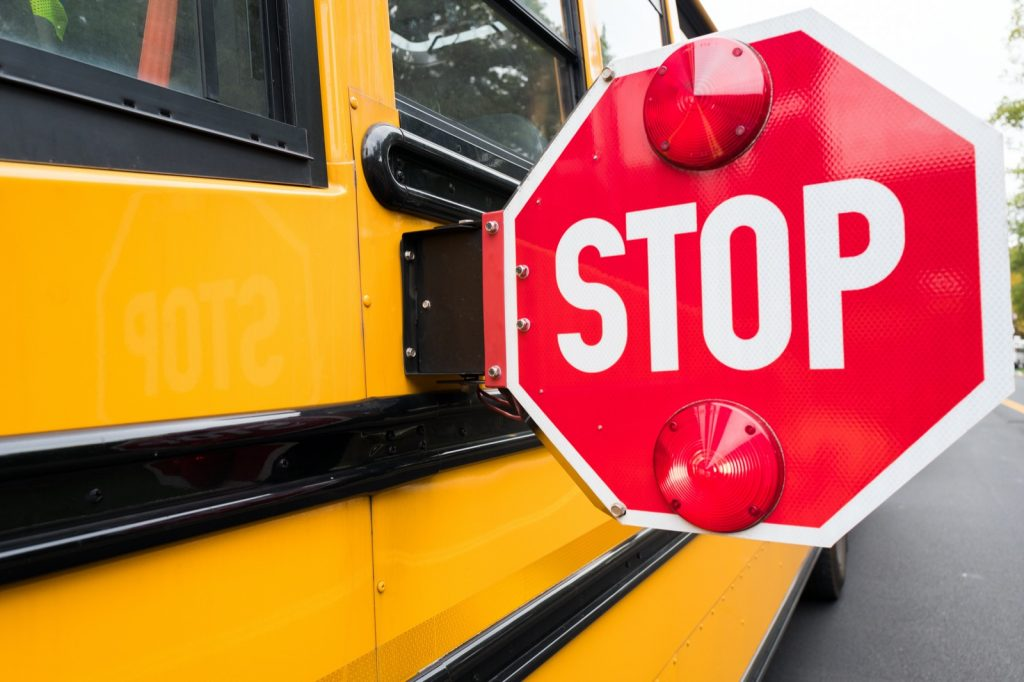 Closeup of a yellow school bus with a red stop sign on the side of the bus