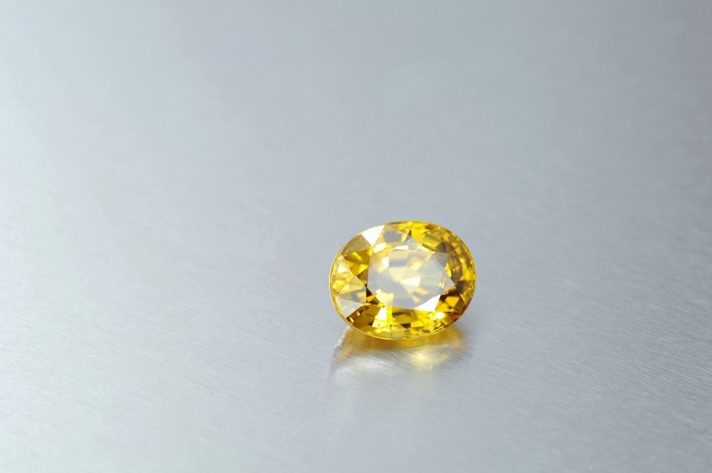 Oval shaped bright yellow zircon gemstone on light gray aluminium metal background